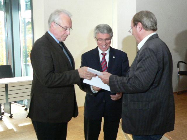 Kleinert (rechts) übergibt die Studie an Landrat Robert Fischbach (links) und Detlef Ruffert Foto: Mank