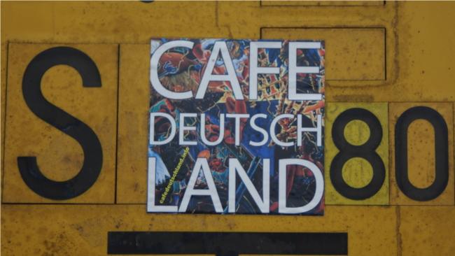 """Simon Reverb und Guido Braun machen sich in Cafe Deutschland """"Gedanken bis der Kopf explodiert"""". Der Aufkleber ist in der Nähe des Bahnhofsvorplatz Gießen...."""
