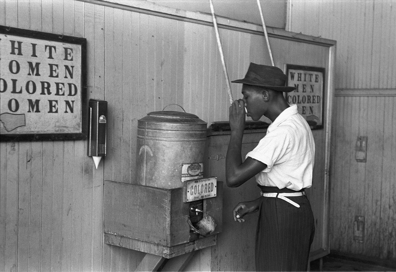 USA 1939: Ein Afroamerkaner trinkt aus einem Wasserbehälter, der ausschließlich farbigen vorbehalten ist. Elle-Chefredakteurin Katell Pouliquen muss am 10. Februar 2017 erleben,dass sie beim Einkaufen in ihrer bretonischen Heimatstadt St. Brieuc mit ihren beiden Söhnen, die dunkelhäutig sind, ebenfalls wegen deren Hautfarbe beschimpft wird......Bild: Wikipedia.fr Russell Lee, 1939