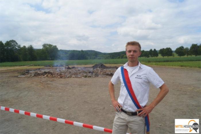 Felix Hartmann, Vorstandsmitglied der Fellinghäuser Burschen- und Mädchenschaft, vor der Absperrung des abgebrannten Sonnwendfeuers. Foto: v. Gallera